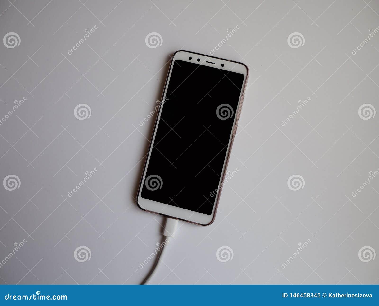 Uno smartphone con un cavo bianco di USB