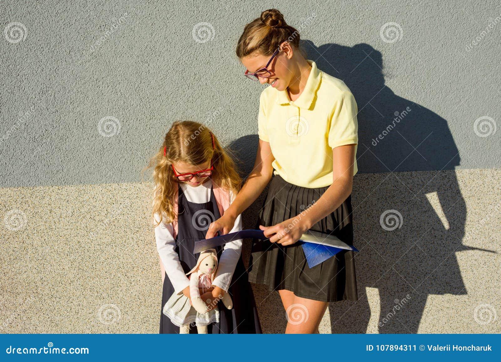 Uno studente della High School aiuta uno studente della scuola elementare ad imparare la t