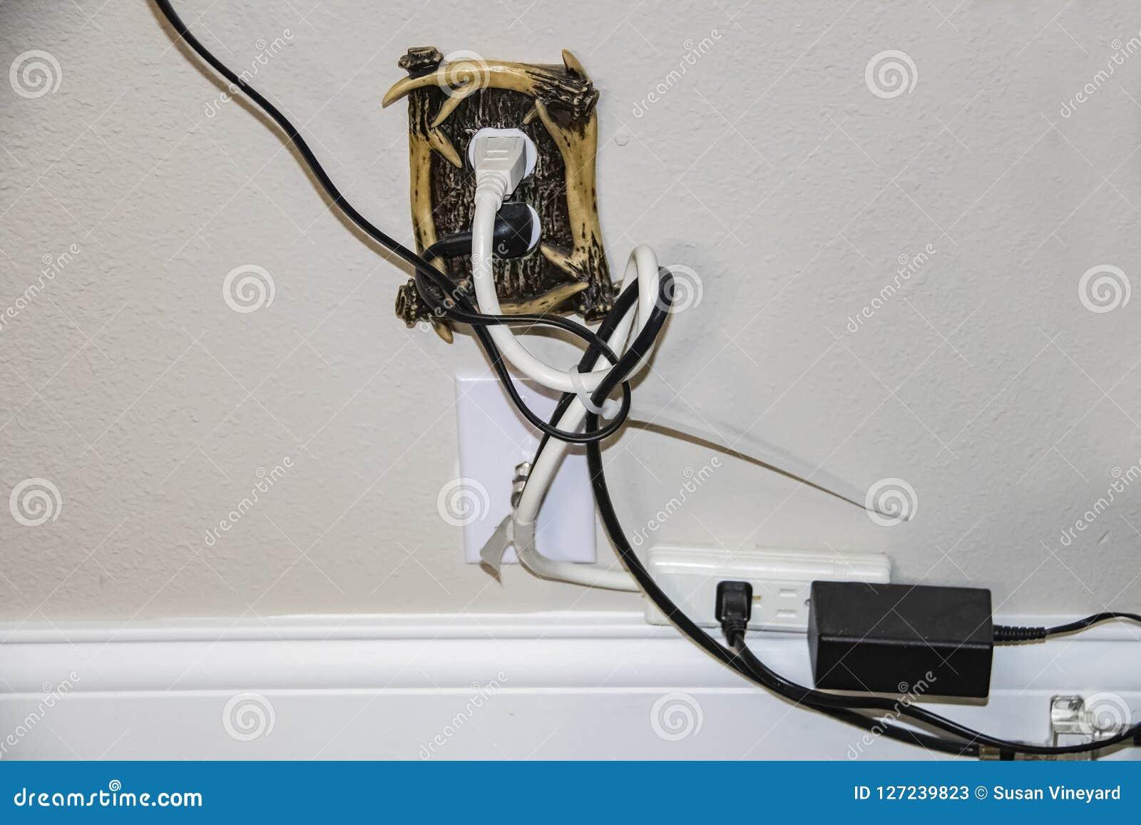 Unordentliche elektrische Schnüre - zu viele verstopfte in eine dekorative Steckdose plus Kabel - alle in einer Verwicklung