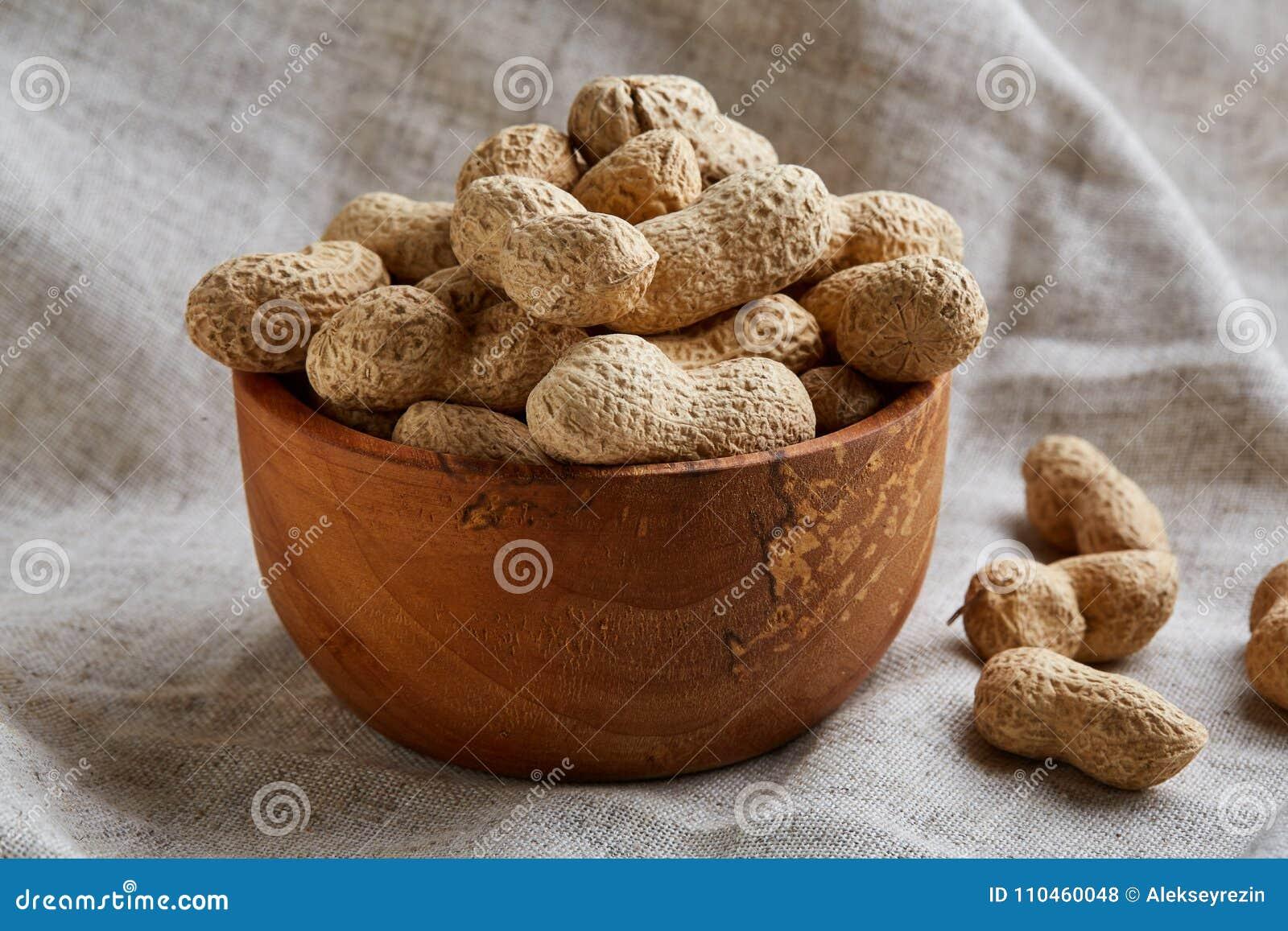 Unpeeled jordnötter i den keramiska bunkecloseupen, selektiv fokus