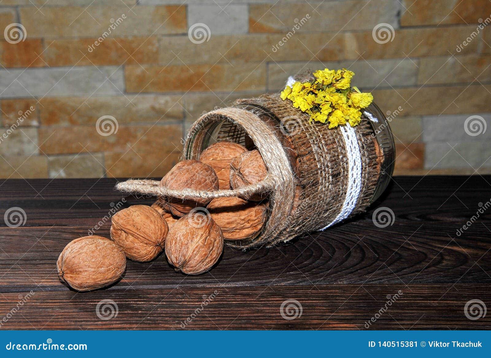 Unpeeled orzechy włoscy w puszce w postaci kosza na drewnianym stole