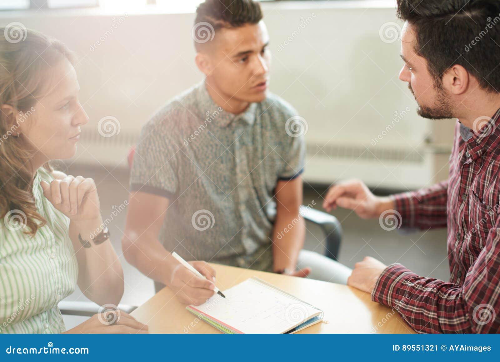 Unposedgroep creatieve bedrijfsondernemers in een open brainstorming van het conceptenbureau samen op een digitale tablet