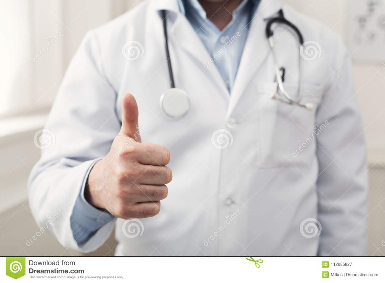 Unrecognizable doctor showing thumb up gesture