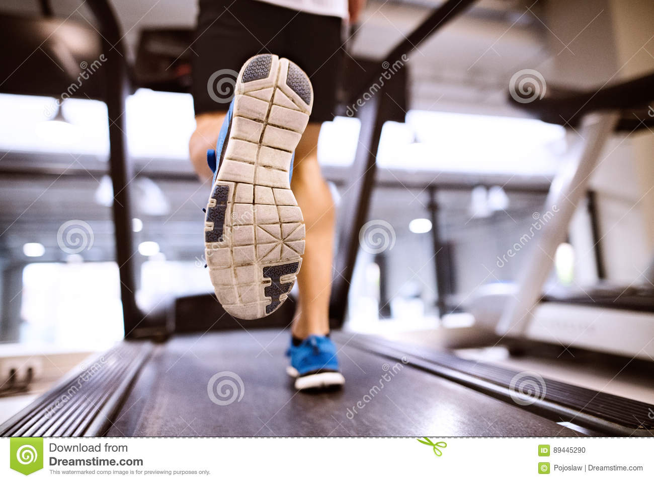 Unrecognizable fit hispanic man in gym running on treadmill.