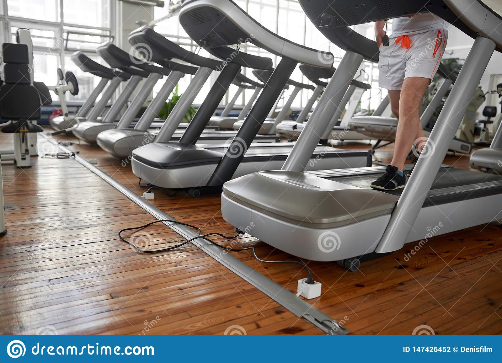 Unrecognizable man on treadmill during his training in gym.