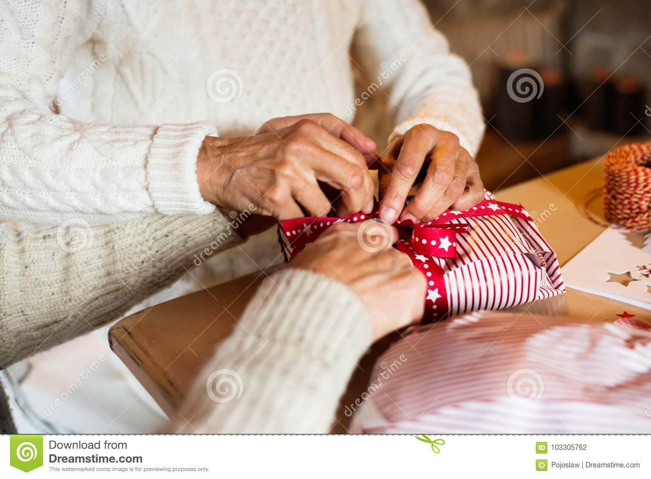 Unrecognizable Senior Couple In Sweaters Wrapping Christmas Gift ...