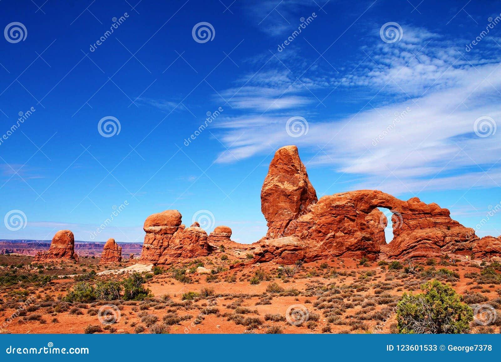 Unregelmäßige Felsformationen mit Berggipfeln und Bogen, über einer Wüstenlandschaft in Utah