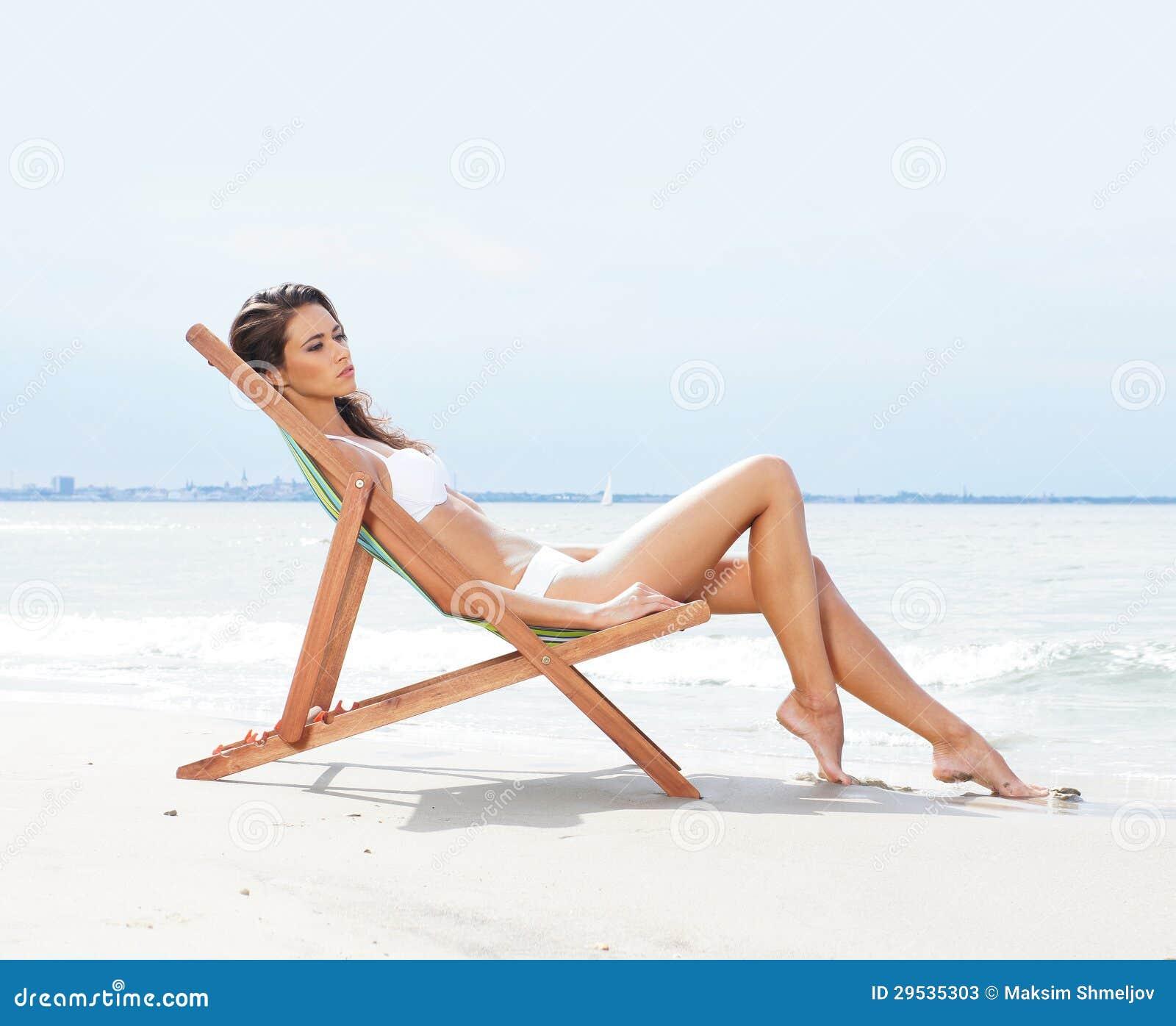 Uns jovens e um brunette do ajuste que relaxa em uma praia bonita