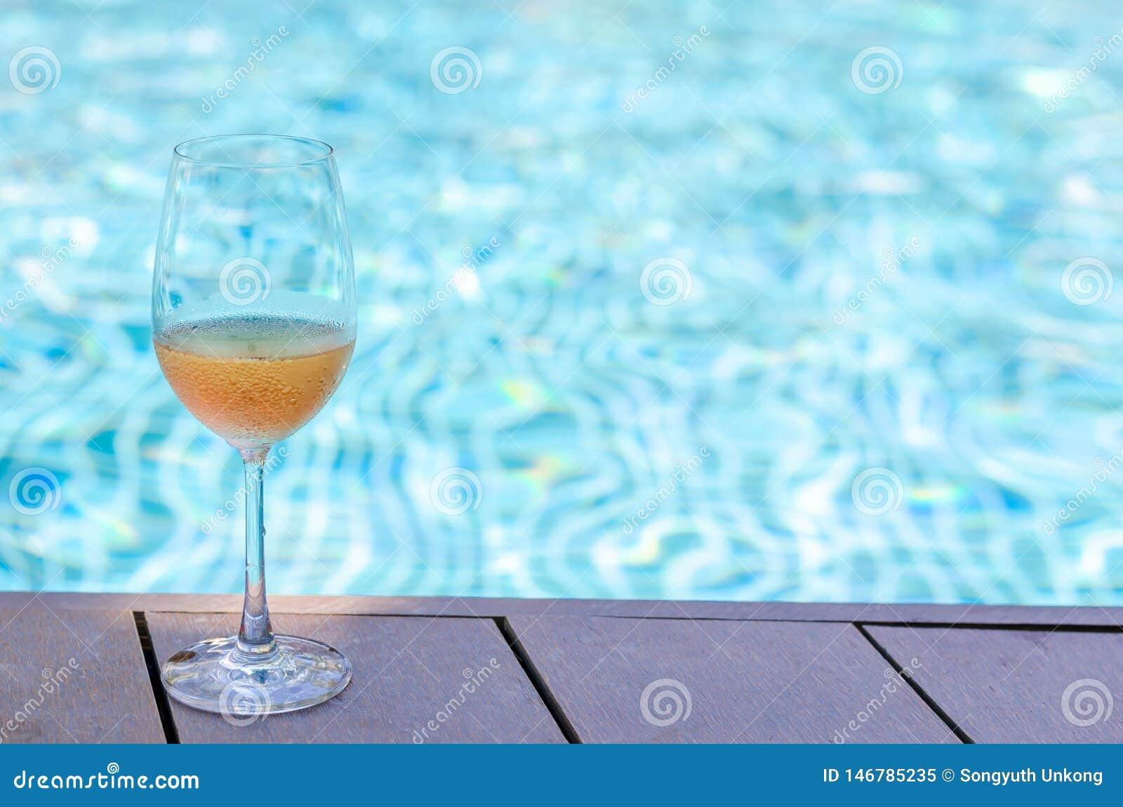 Uns vidros do vinho de Rosa postos sobre a piscina