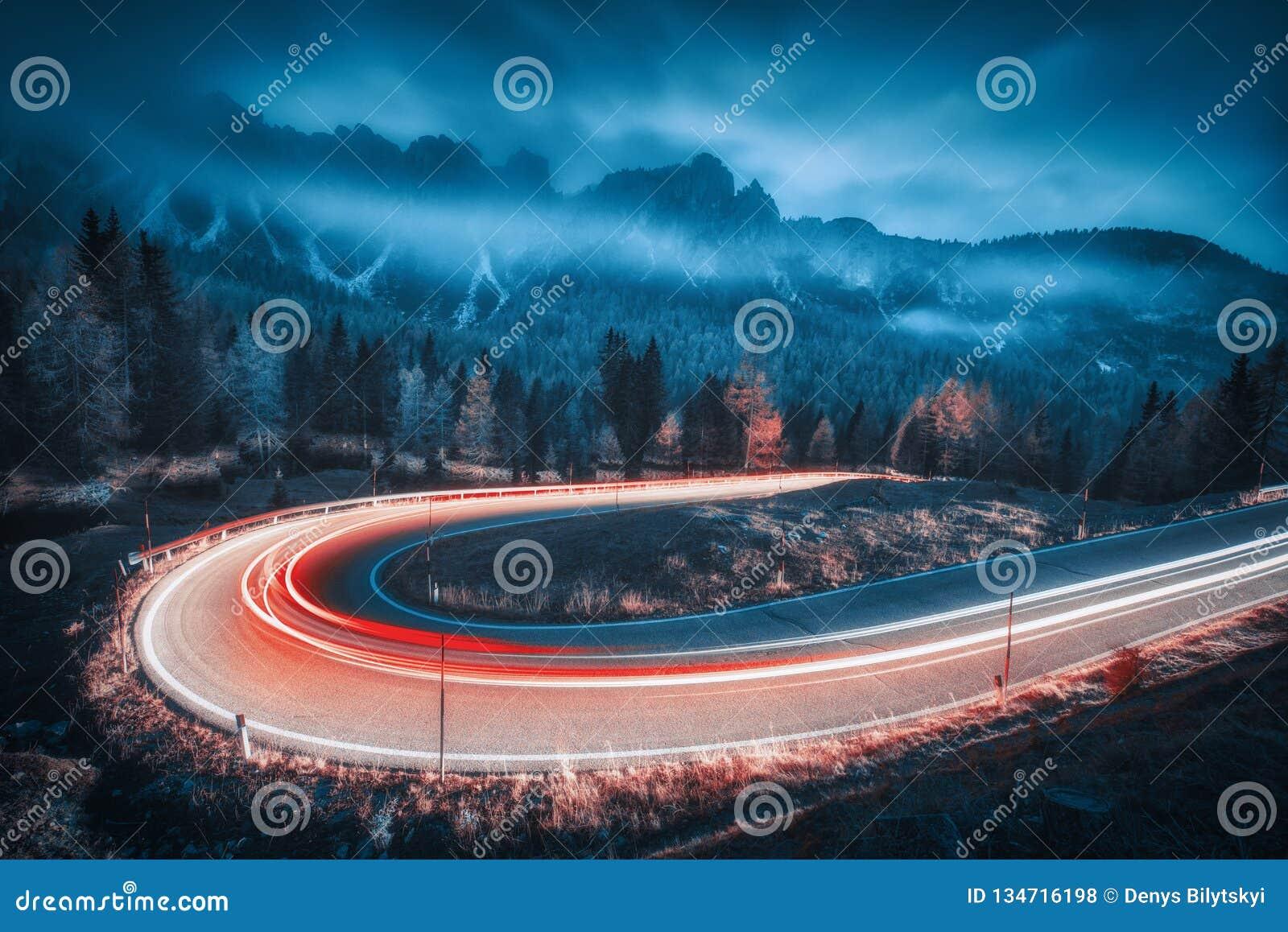 Unscharfe Autoscheinwerfer auf kurvenreicher Straße in den Bergen