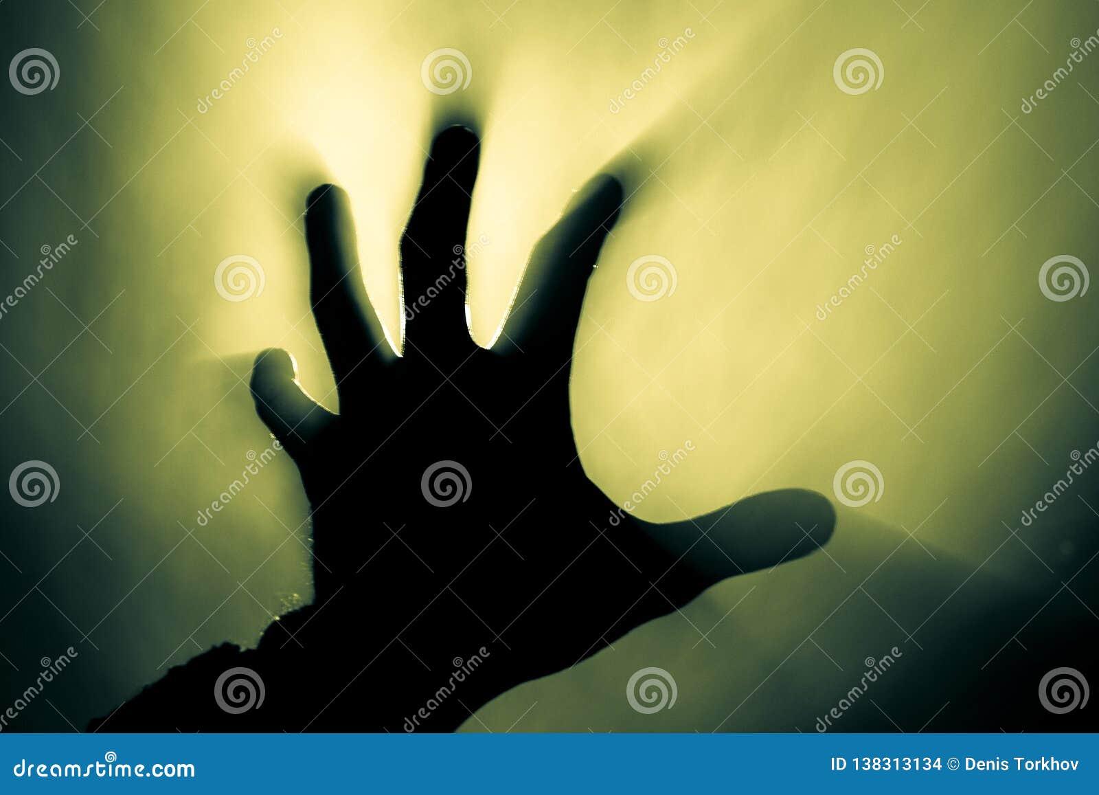 Unscharfe Hand im Rauche in einem Feuer im grellen Licht der Sonne