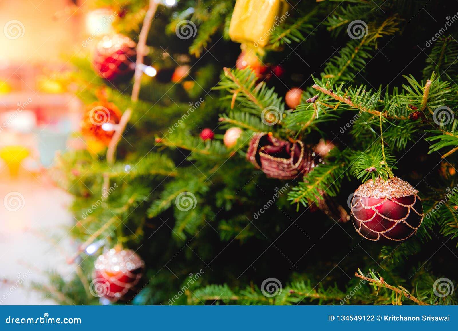 Unscharfe Zusammenfassung des Weihnachtsbaums verziert mit hängende Flitterball-, heller und kleinergeschenkbox