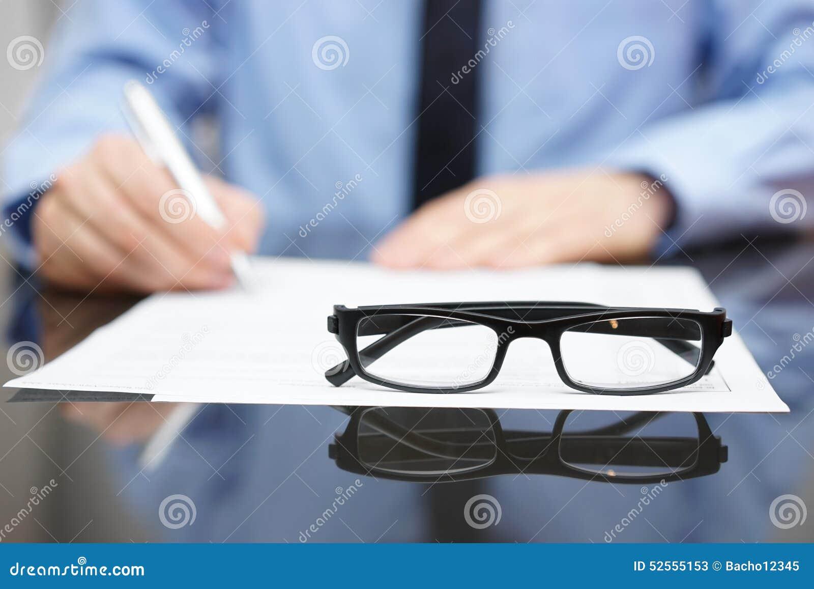 Unscharfer beschäftigter Unternehmer im Hintergrund mit Fokus auf Gläsern