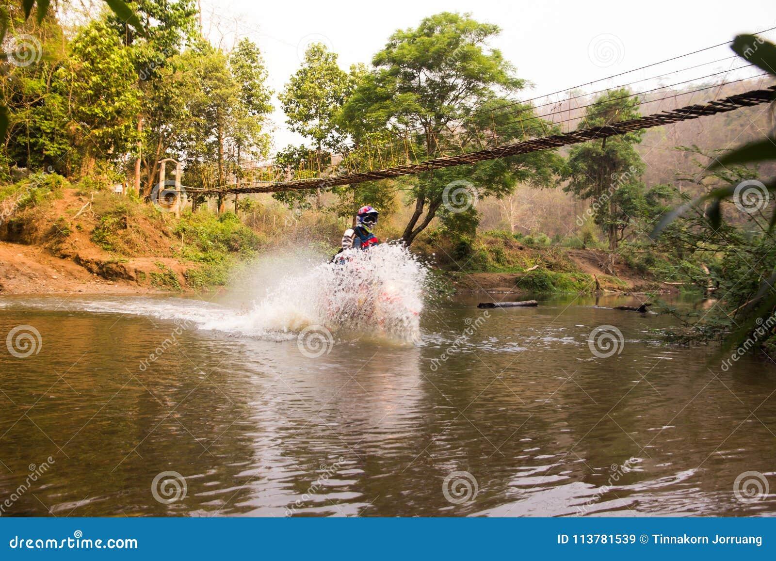 Unscharfer Bild enduro Motorradrennläufer fuhr in das Wasser