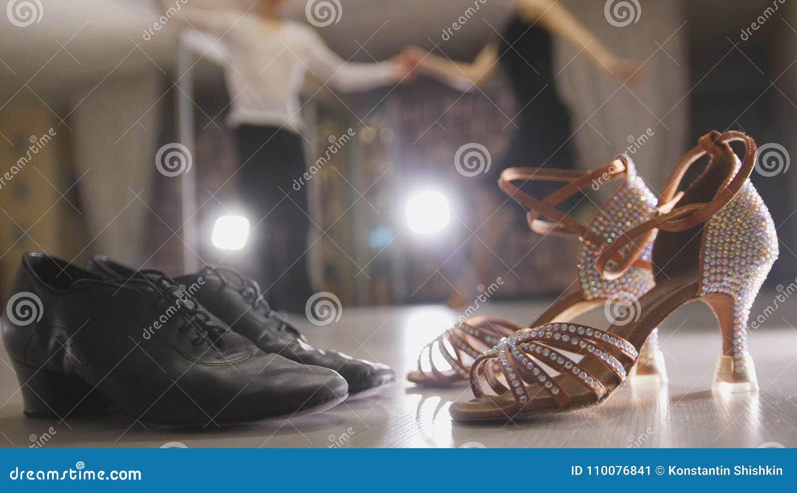Unscharfer tanzender lateinischer Tanz der Professioneller und der Frau in den Kostümen im Studio, zwei Paarballsaalschuhe im Vor