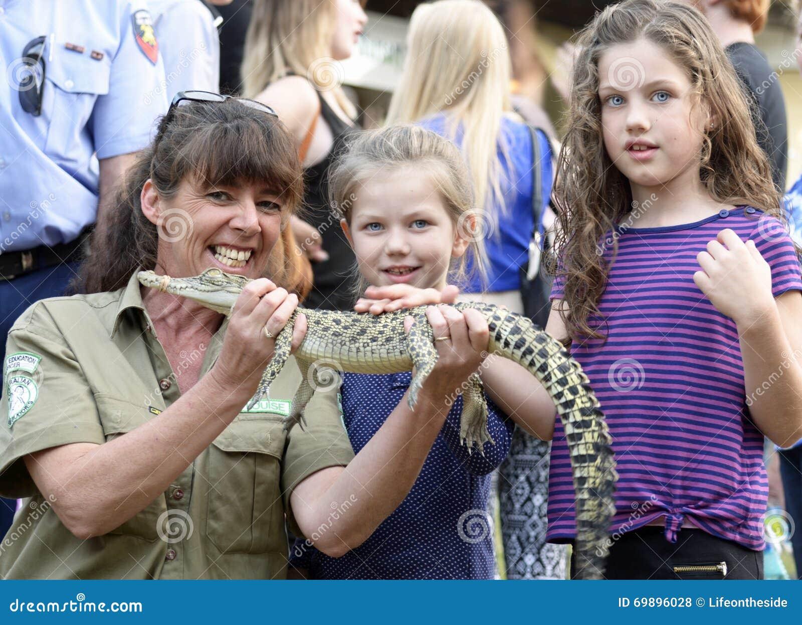 Unterrichtende Kinder des australischen Frauen-Wildhüters der wild lebenden Tiere über gebürtige Krokodile an der lokalen Messe