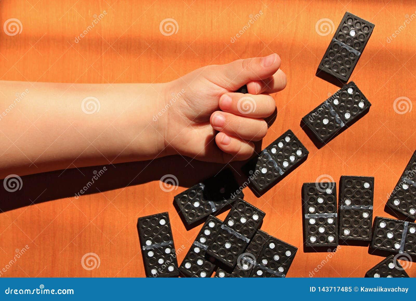 Unterrichtende Kinder, zum des Dominospiels auf einem hölzernen Hintergrund zu spielen