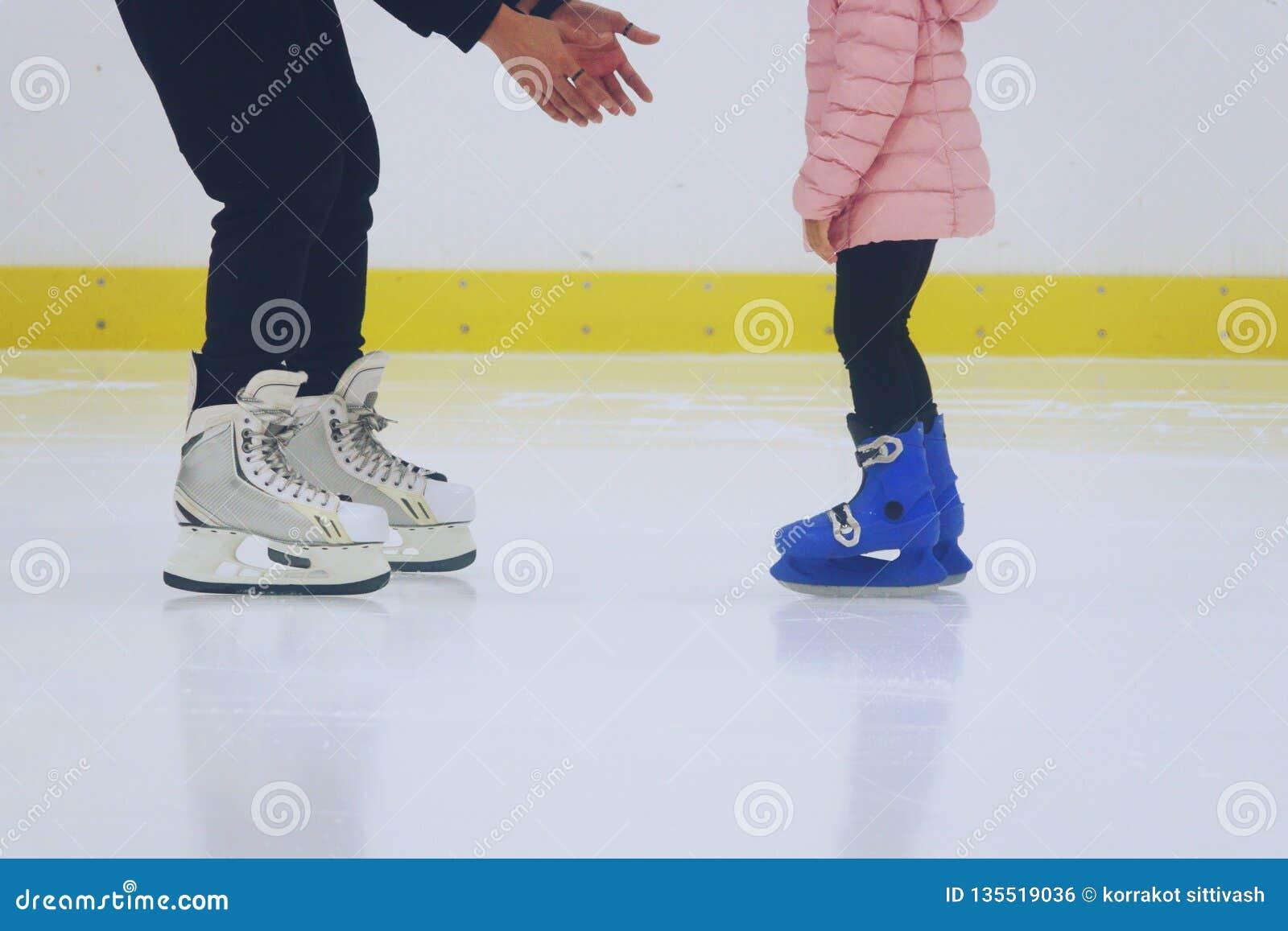 Unterrichtende Tochter des Vaters, zum am Schlittschuh laufen der Eisbahn eiszulaufen