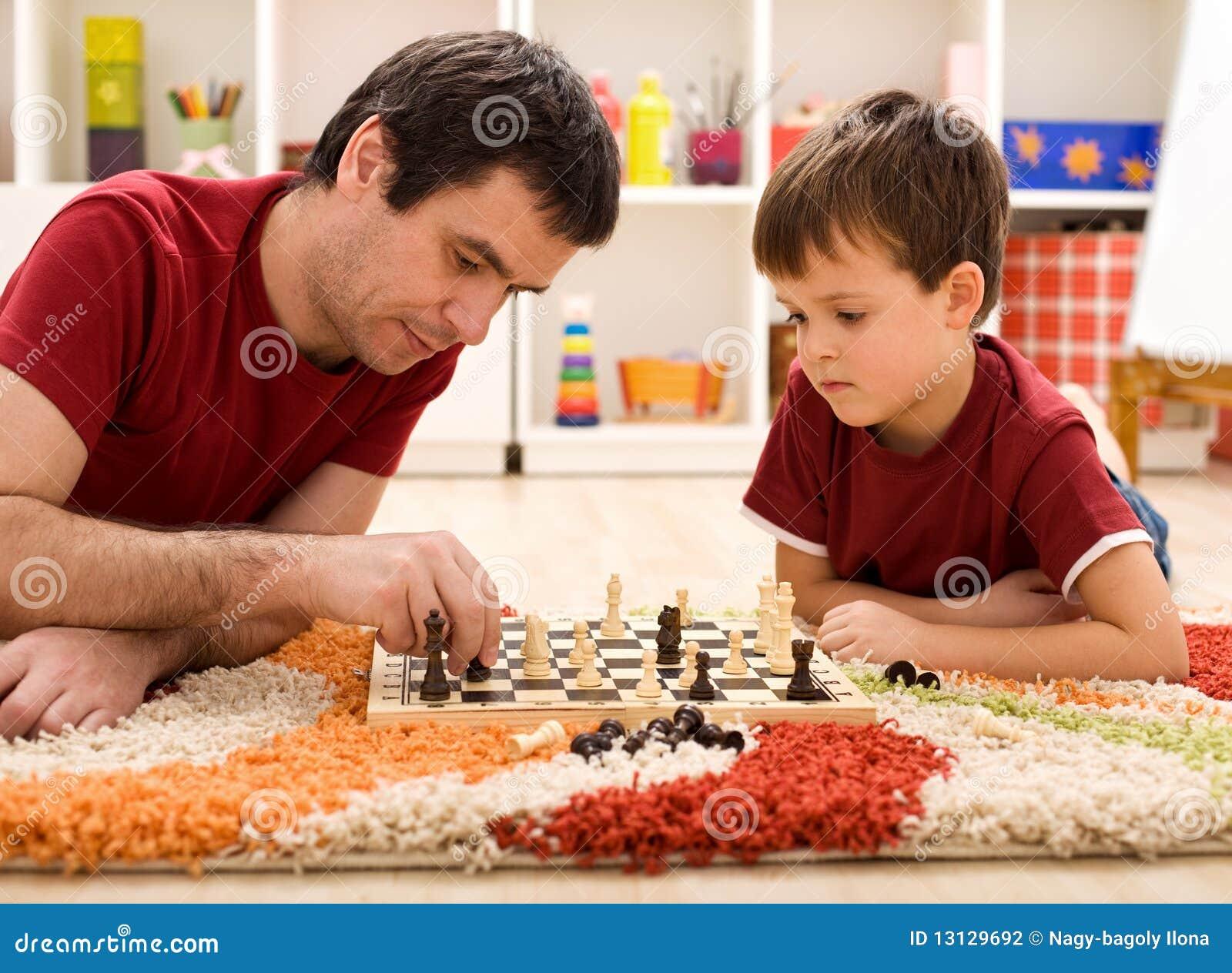 Unterrichtender Sohn des Vaters die Richtlinien des Schachs