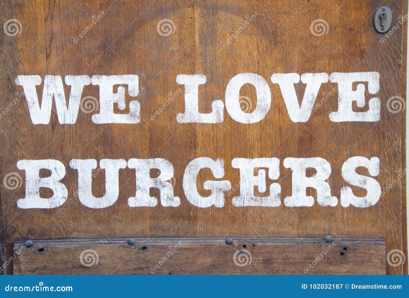 Unterzeichnen Sie `, das wir Burger ` auf der hölzernen Wand lieben