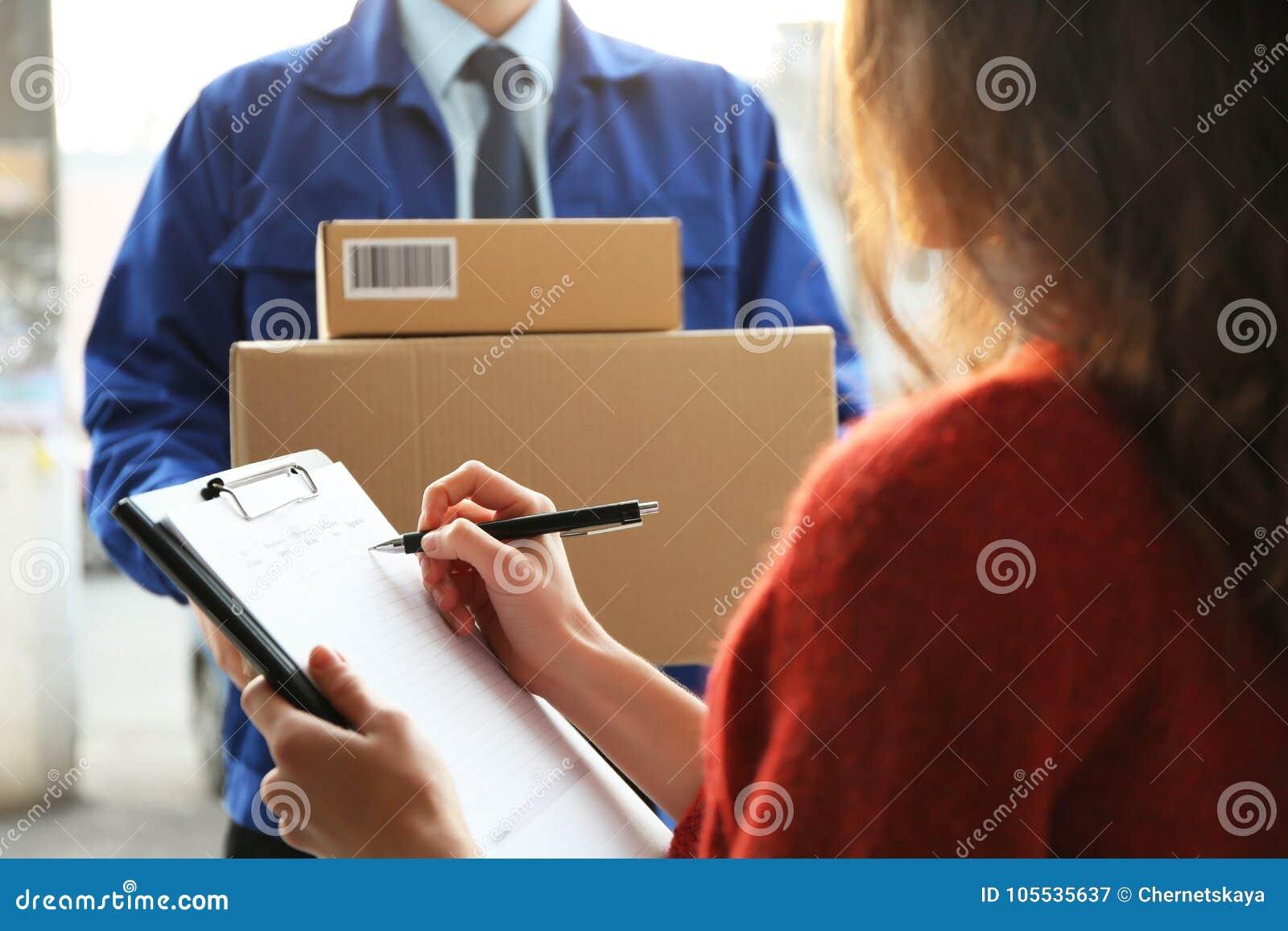 Unterzeichnende Dokumente der jungen Frau, nachdem Pakete empfangen worden sind