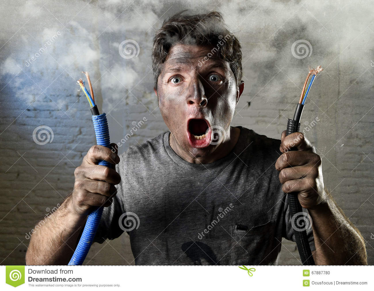Untrained man joining electrical cable suffering electrical accident with dirty burnt face in funny shock expression