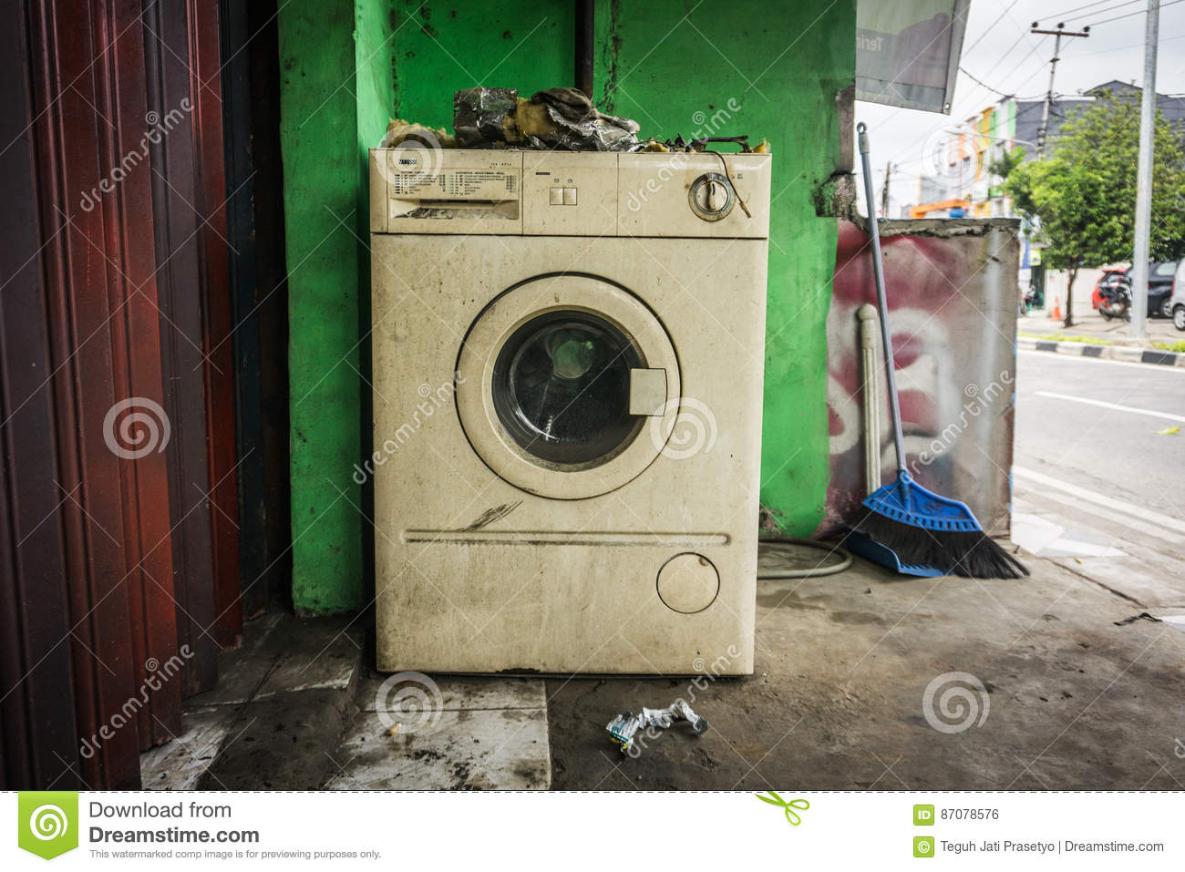 The unused white washing machine with front door near green wall and a broom photo abandoned in a street photo taken in