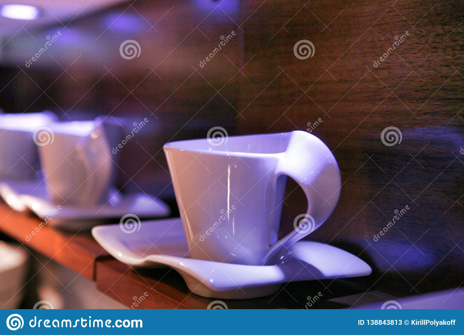 Unusual porcelain white cups and saucers displayed on a wooden shelf.