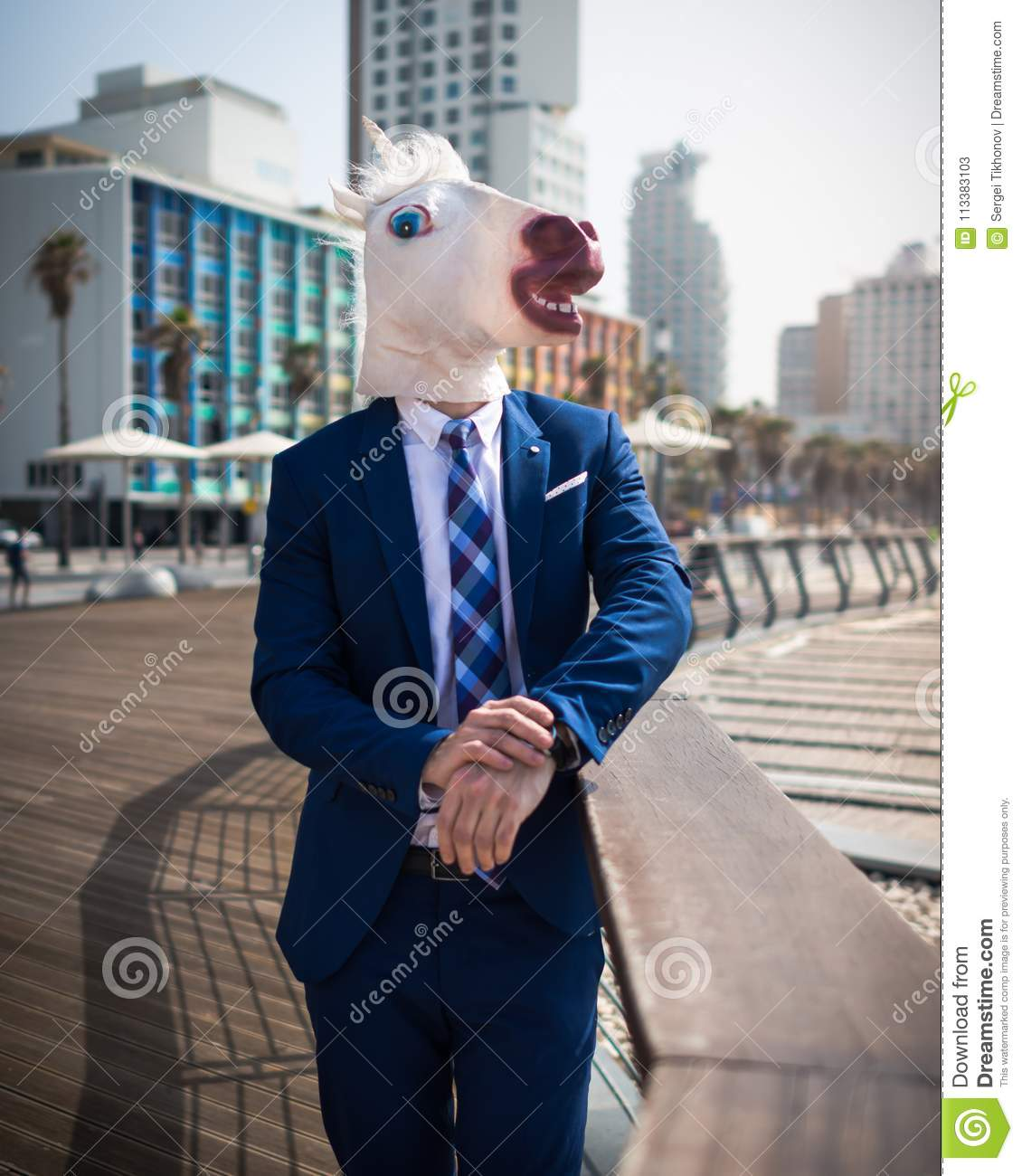 Unusual young man in elegant suit stands on the city waterfront