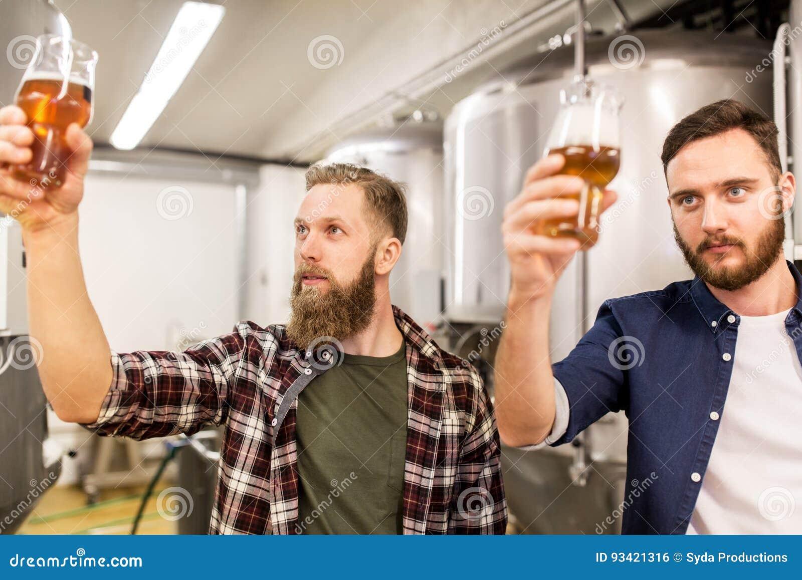 Uomini che bevono e che provano la birra del mestiere alla fabbrica di birra