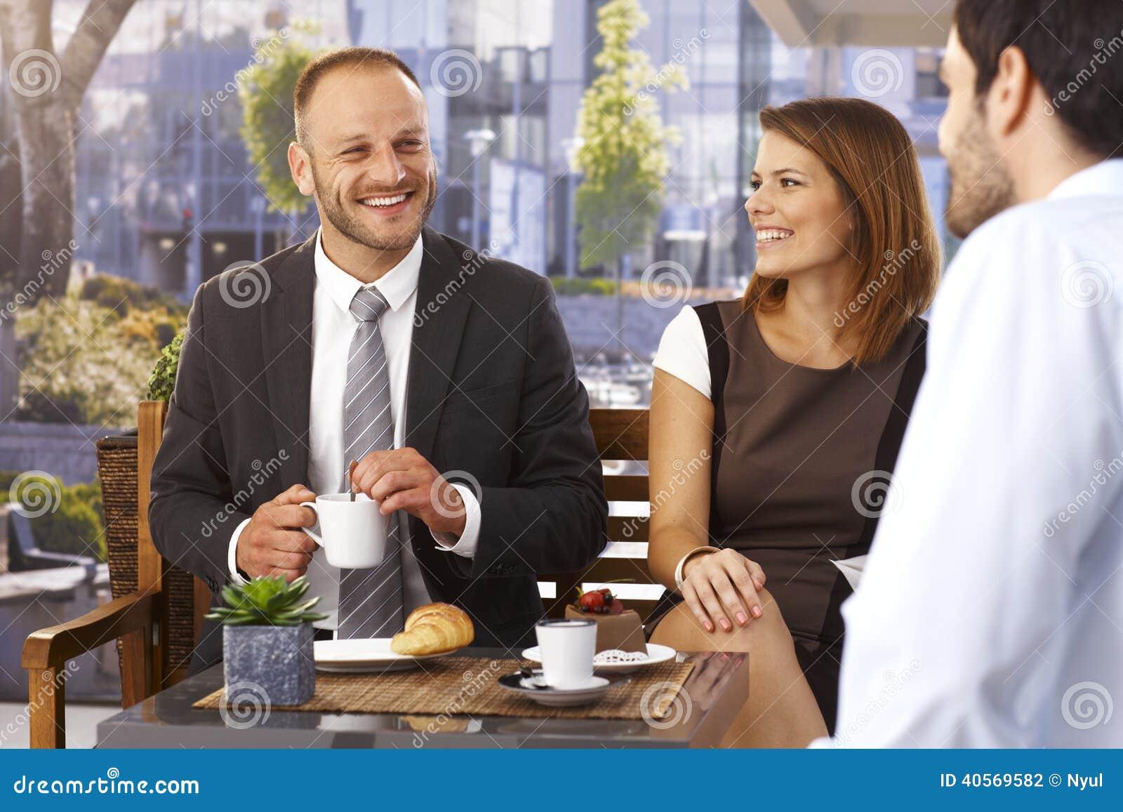 Uomini d affari e donna di affari che si rilassano al caffè