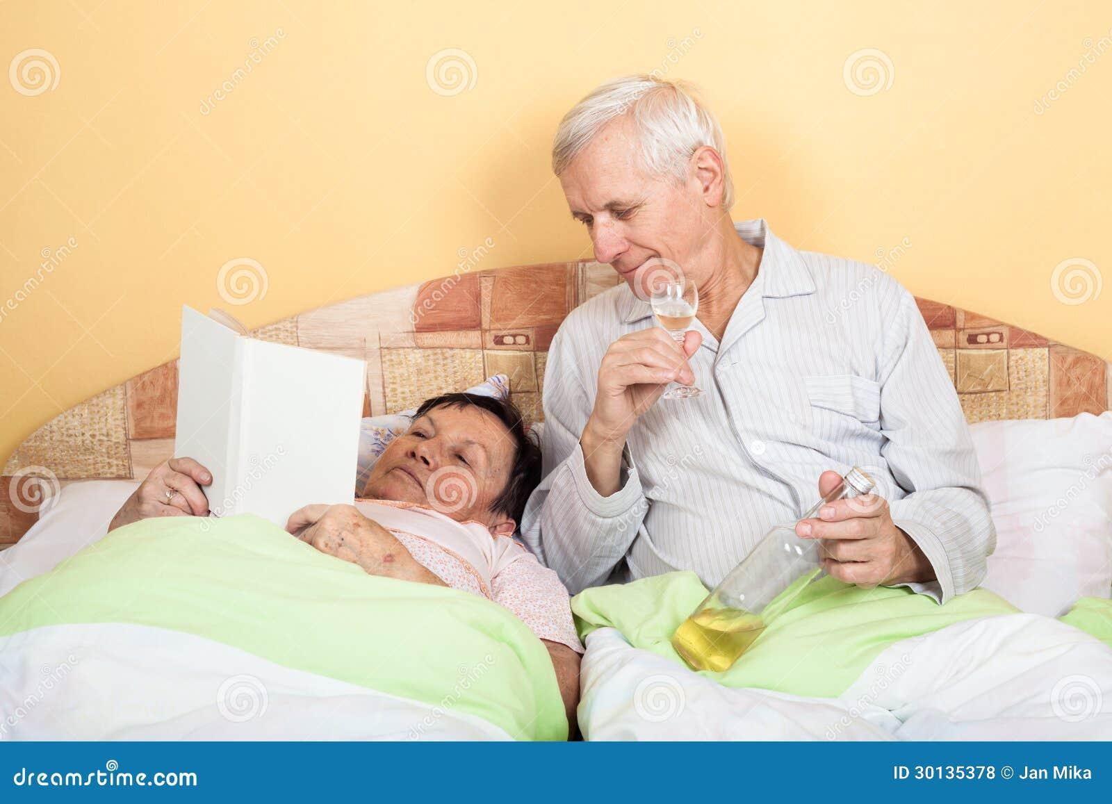 Gli anziani divertenti si rilassano con l 39 alcool a letto fotografie stock libere da diritti - Foto di donne a letto ...