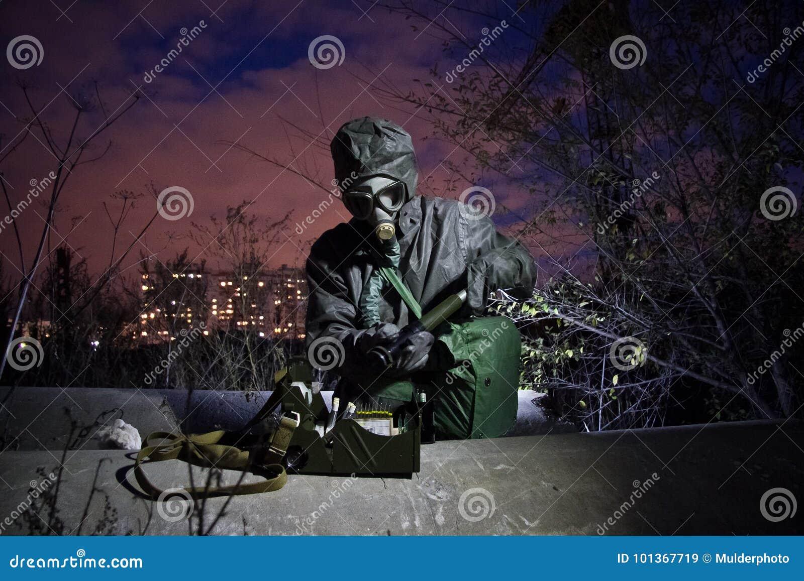 Uomo in abbigliamento chimico protettivo e maschera antigas isolata con il dispositivo di rilevazione chimico nella zona di conta