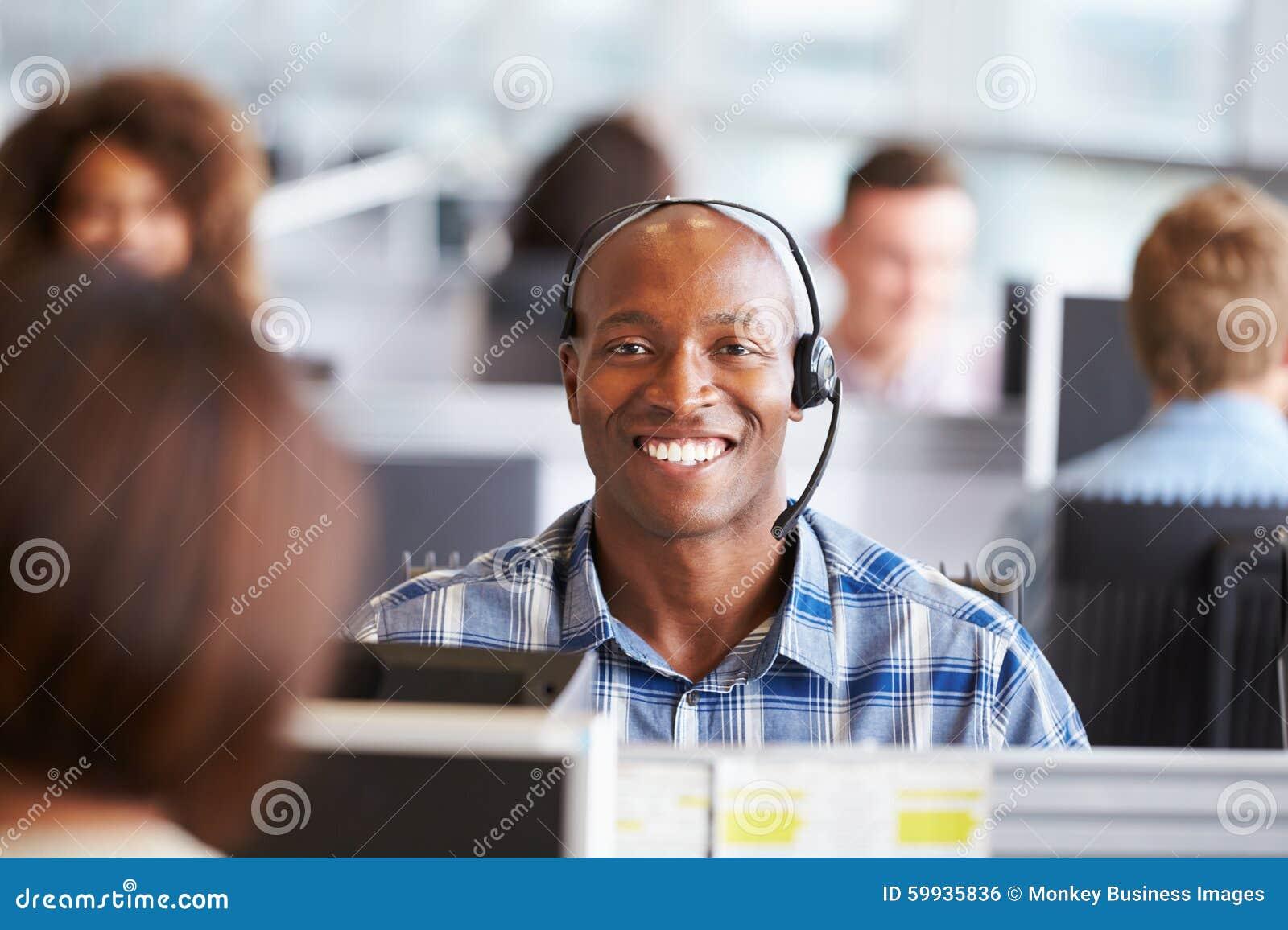 Uomo afroamericano che lavora nel call-center, sguardi alla macchina fotografica