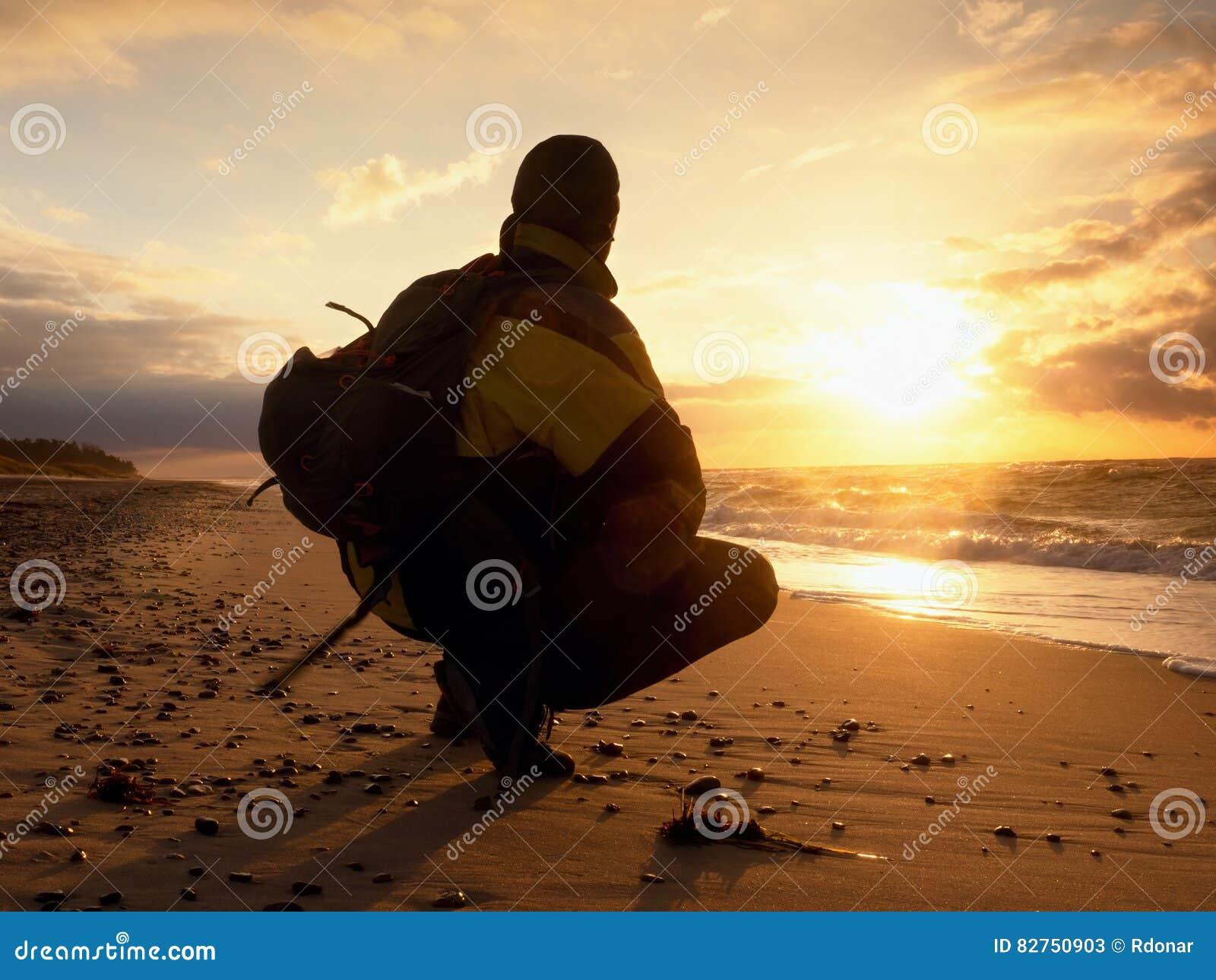 7df39c4bab L'uomo si siede al mare di sera La viandante con lo zaino si siede  nell'occupare la posizione lungo la spiaggia Lo stile d'annata ha  tonificato l'effetto