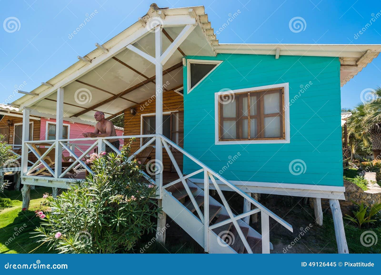 Uomo al portico della casa di spiaggia nella costa for Disegno della casa sulla spiaggia