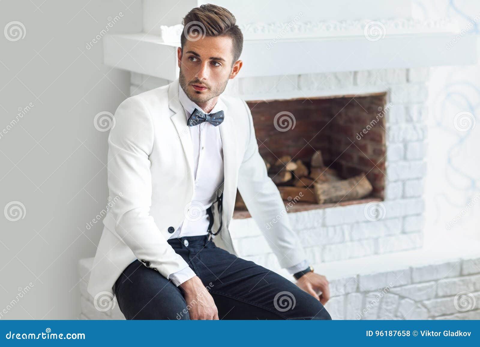 Uomo alla moda bello in vestito elegante bianco che si siede vicino al  camino edae1f89b0d