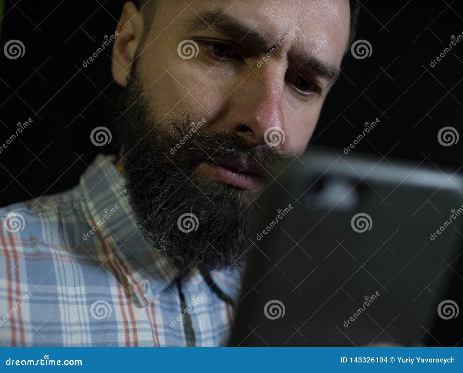 Uomo alla moda con una barba e sguardi dei baffi ad un telefono cellulare con un espressione facciale seria su un fondo nero