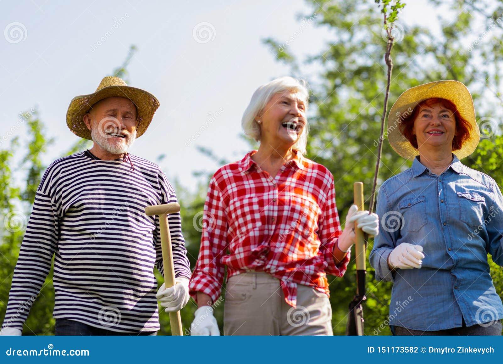Uomo allegro e positivo e donne che si dirigono per piantare gli alberi