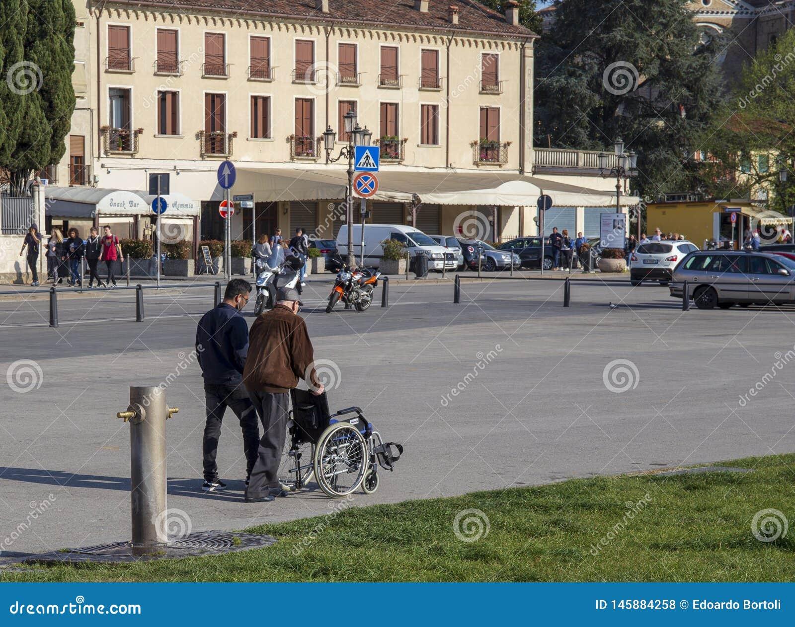 Uomo anziano aiutato da un ragazzo, spinge la sedia a rotelle