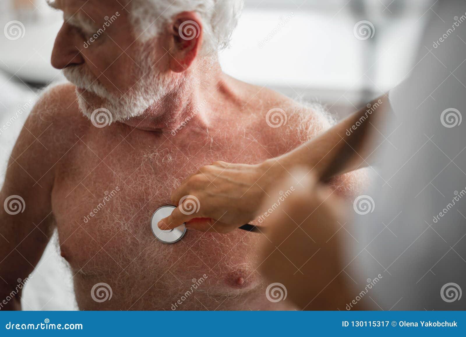 Uomo anziano che si siede sul letto di ospedale durante l esame medico