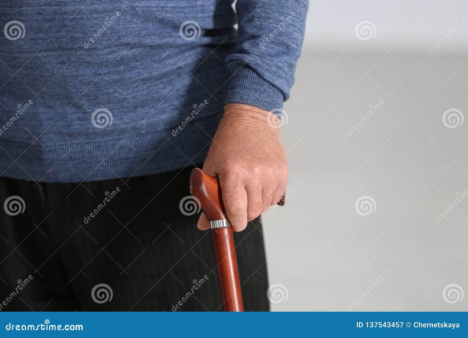 Uomo anziano con la canna di camminata su fondo vago, primo piano della mano