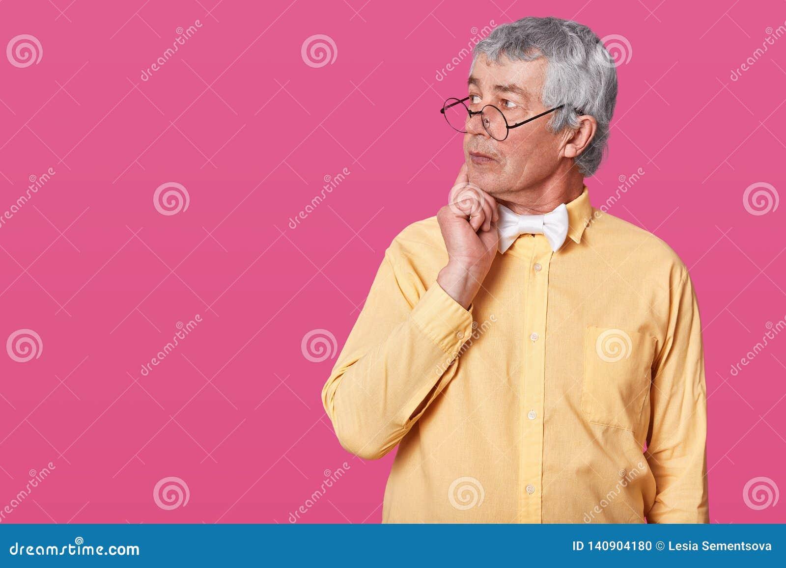 Uomo anziano premuroso con i vetri arrotondati neri sul naso L anziano anziano guarda da parte e tiene la mano destra sul mento D
