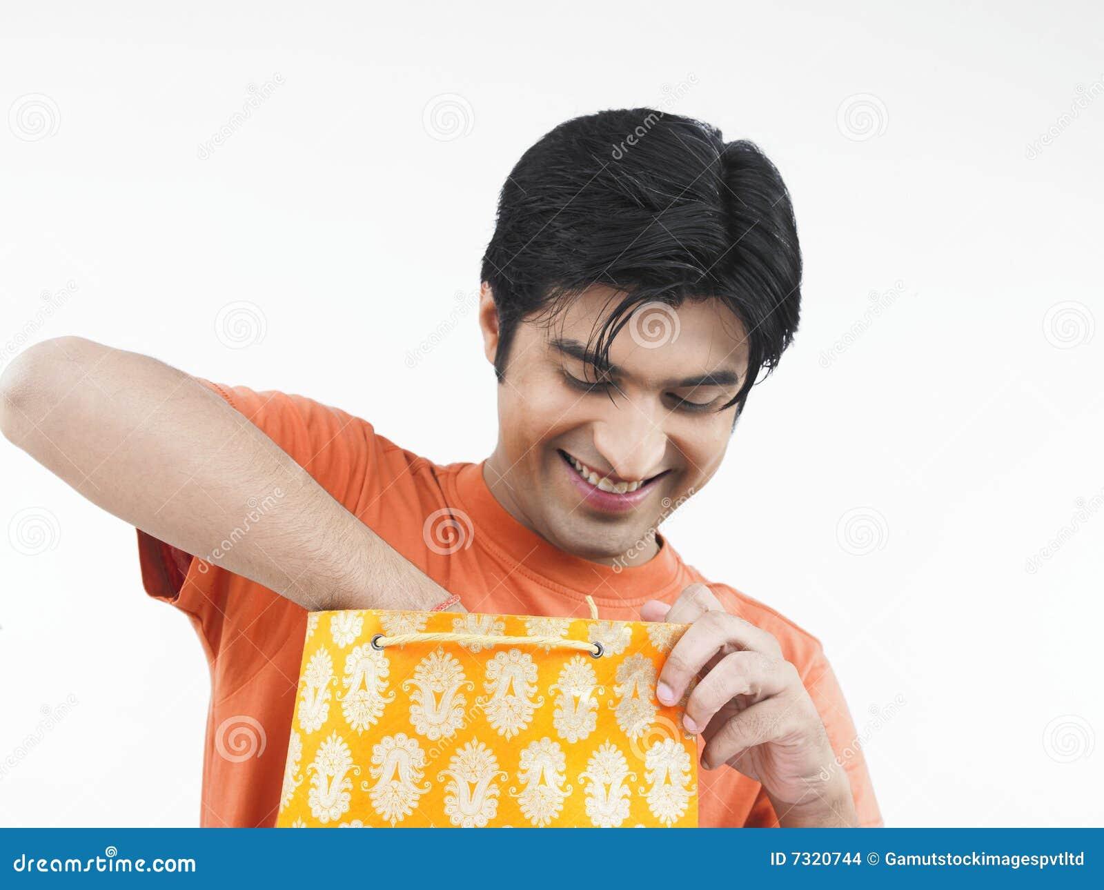 Uomo asiatico che controlla il suo sacchetto di acquisto