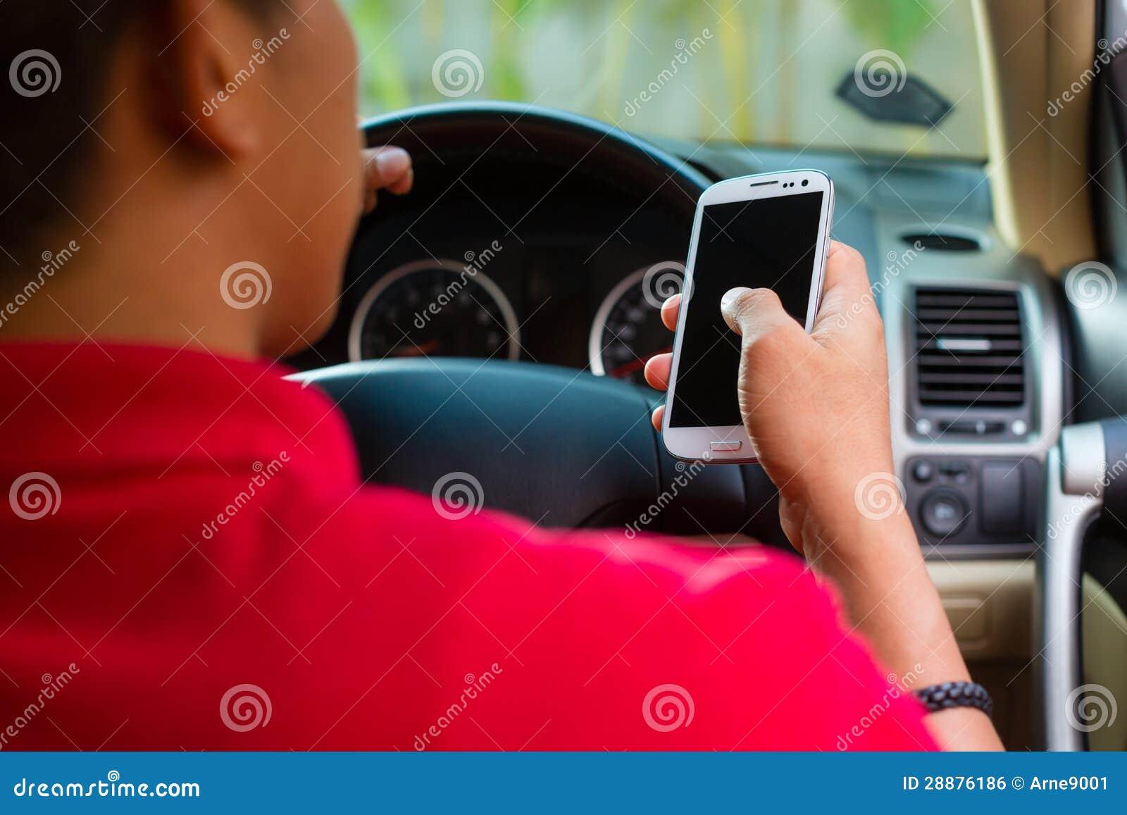Uomo asiatico che texting mentre guidando
