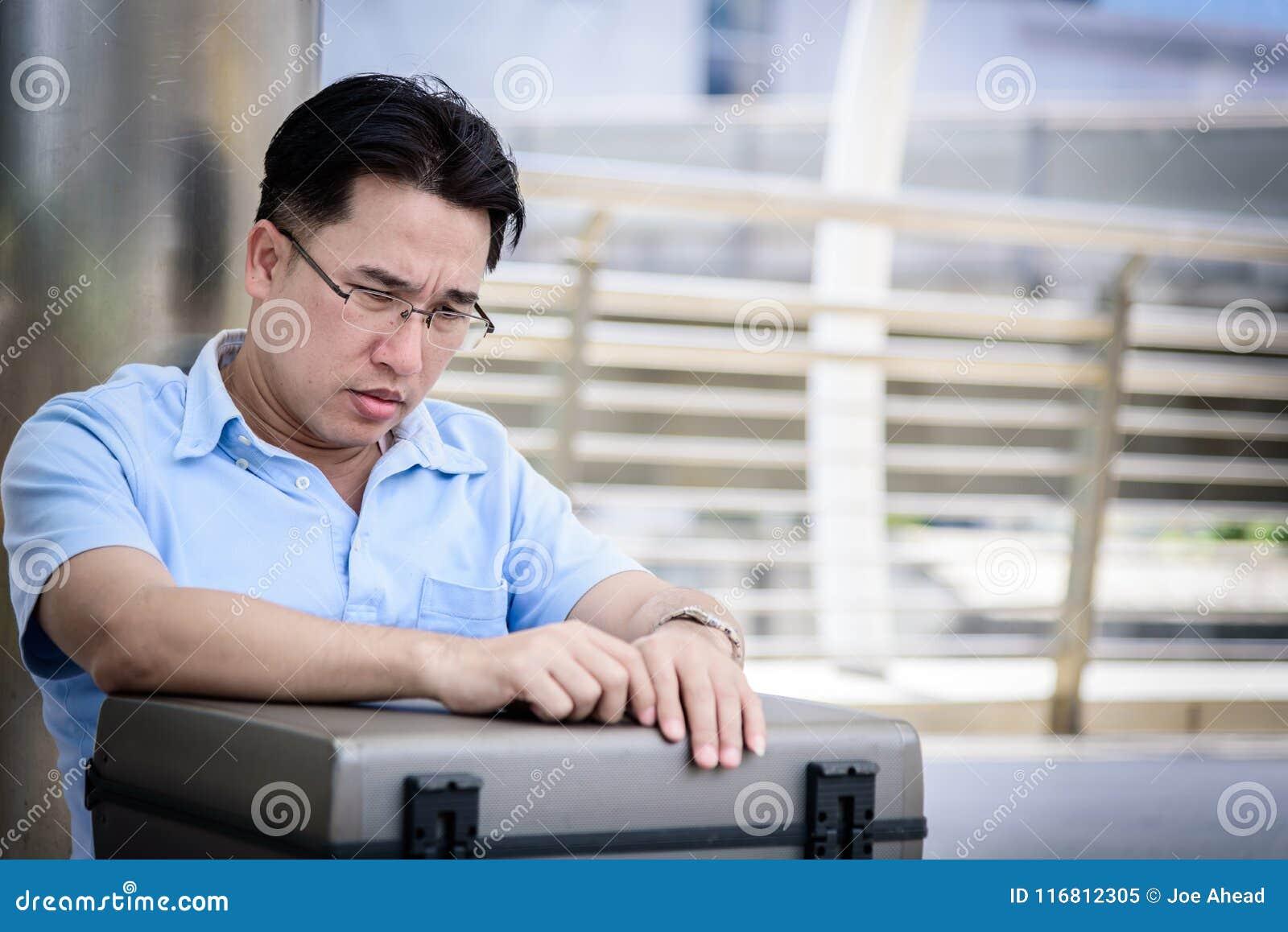 Uomo asiatico di affari che si siede nella depressione con la borsa nera