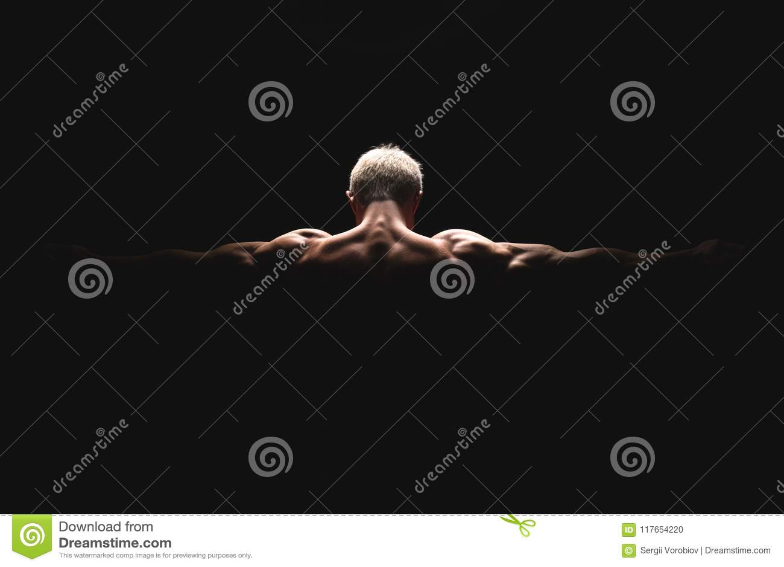Uomo atletico di potere bello alla luce drammatica Forte culturista con le spalle perfette, bicipite, tricipite, parte posteriore