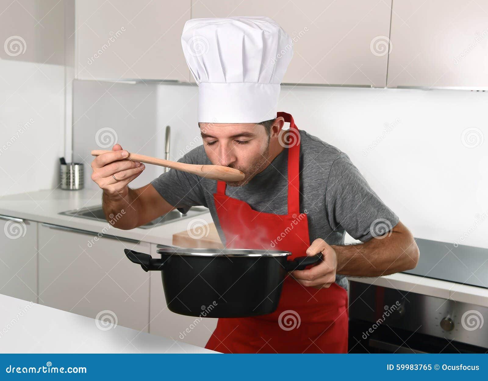 Il giovane uomo attraente in cappello del cuoco unico e la prova rossa del  grembiule del cuoco condiscono mentre cucinano il vaso della tenuta della  ... 796ff2a9e9c1