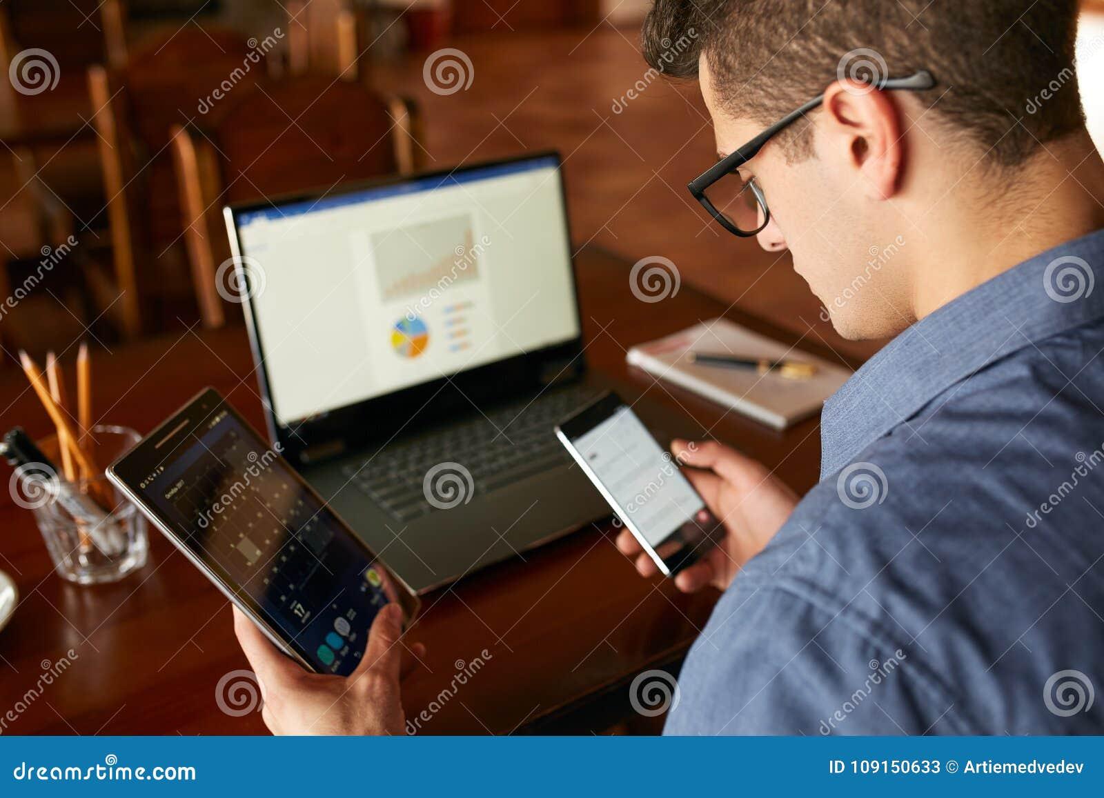 Uomo attraente nel funzionamento di vetro con i dispositivi di Internet elettronici multipli L uomo d affari delle free lance ha