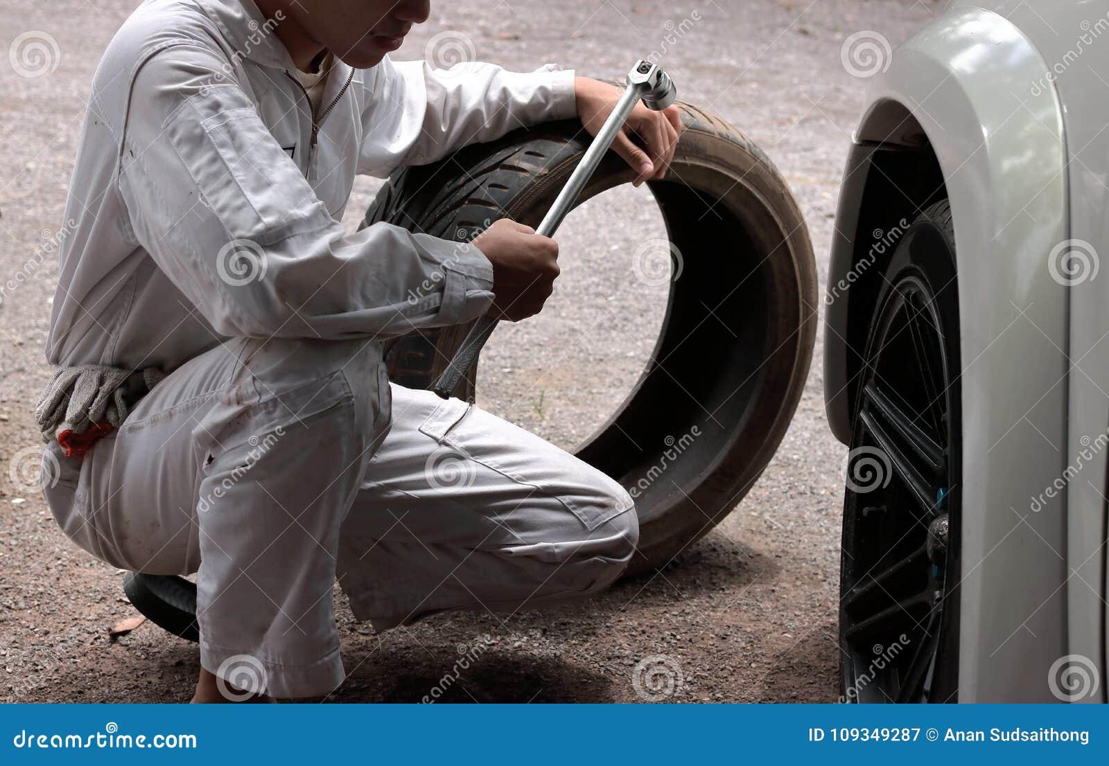 Uomo automobilistico del meccanico in uniforme con la gomma e la chiave per l automobile di riparazione ai precedenti del garage